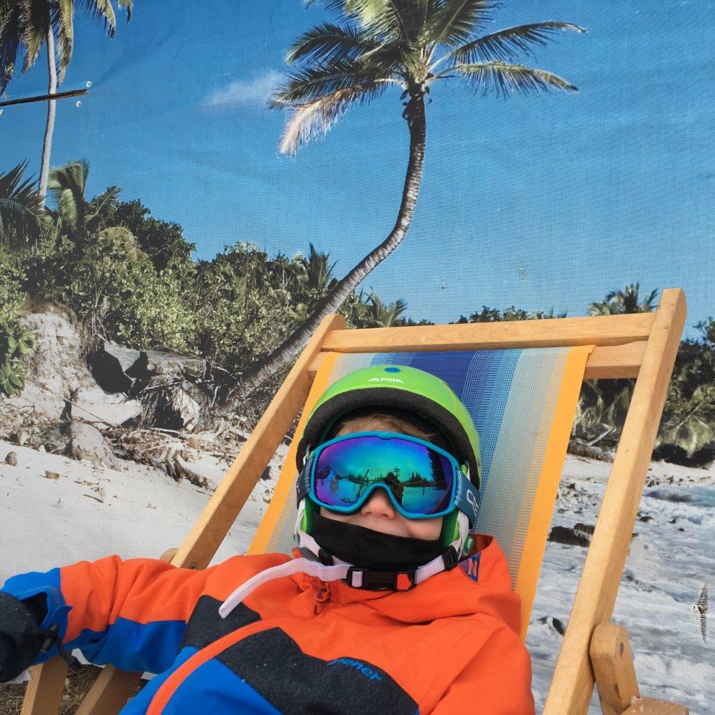 Jonas beim Chillen im Liegestuhl vor Palmenlandschaft. Schnappschuss aus Jungholz.